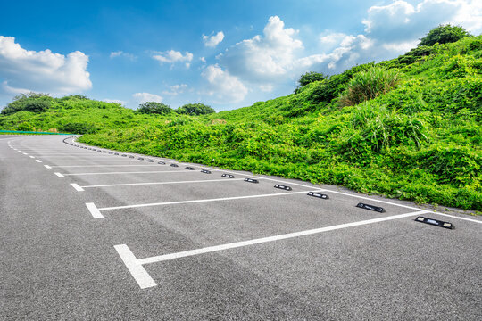 Asphalt parking lot and green mountain nature landscape.