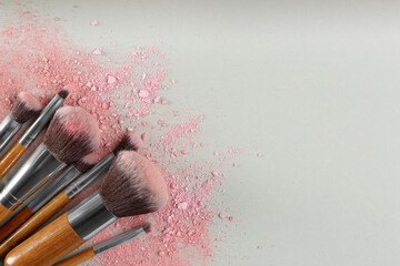 Obraz Makeup brushes and scattered eye shadows on light grey background, flat lay. Space for text - fototapety do salonu
