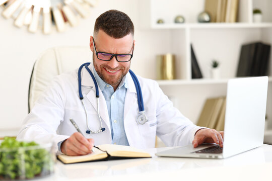 Male doctor working at his workplace in private clinic or hospital