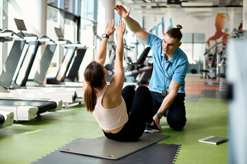 Obraz Athletic woman exercising sit-ups with help of personal trainer in a gym. - fototapety do salonu