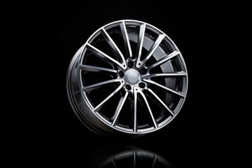 Fototapeta sporty alloy wheels . the rim on a black background. car tuning auto parts obraz