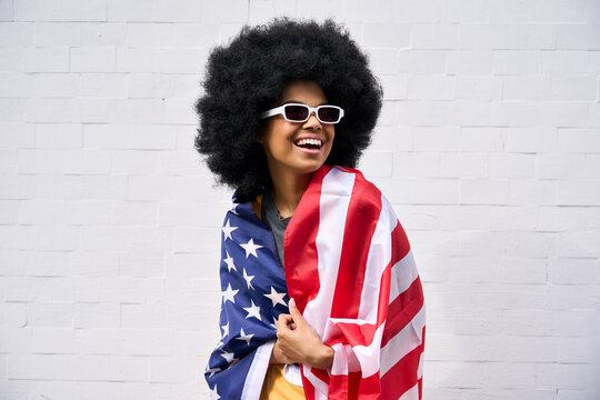 Happy smiling African American teenager wearing sunglasses wrapped in usa flag celebrating july 4th forth independence day of united states. Patriotic portrait on white bricks wall background.