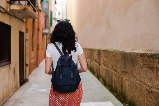 Rear view of a young woman with a backpack walking down a lonely city alley