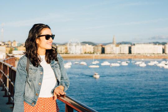 Happy young tourist woman enjoying the view of San Sebastian bay in Spain