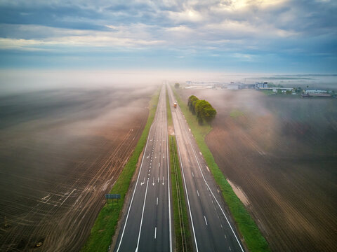 Aerial view of a highway covered by fog. Early misty morning. Road in rainy spring summer fields.