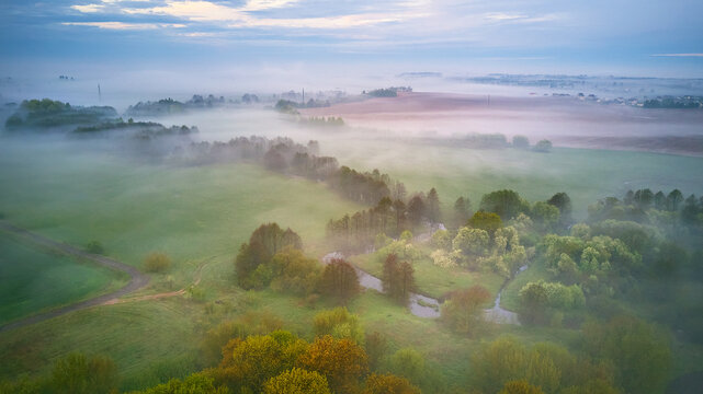 Summer cloudy rainy foggy morning panorama. Rural misty river, fields, meadow, village. Spring overcast moody weather. Blooming trees