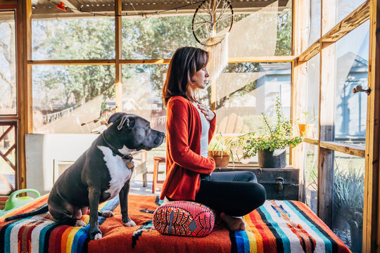 Woman meditating with eyes closed on sunlight filled porch with Pitbull pet dog