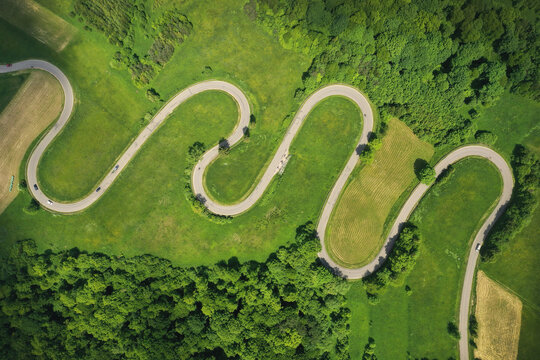 Aerial drone view of winding road between green forest