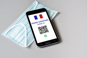 Fototapeta Passe sanitaire Covid-19, application en vigueur le 9 juin 2021 en France. Téléphone portable et masque. obraz