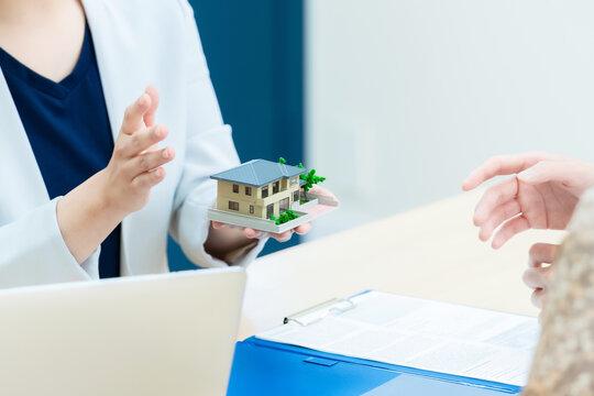 住宅模型を持って説明する女性 ハウスメーカー 設計士