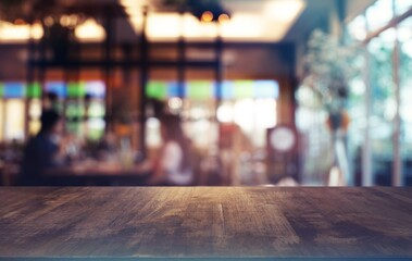 Obraz Empty wooden table in front of abstract blurred background of coffee shop . can be used for display or montage your products.Mock up for display of product. - fototapety do salonu