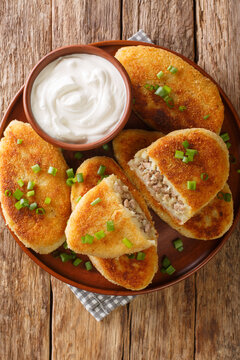 Potato zrazy with meat served with sour cream close-up in a plate on the table. Vertical top view from above