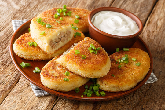 Homemade hot potato zrazy pies with meat filling with sour cream close-up in a plate on the table. horizontal