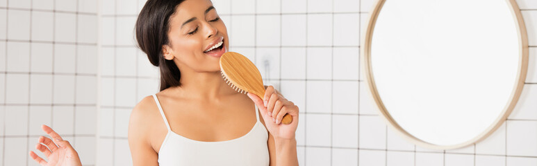 Obraz young african american woman with closed eyes singing with hair brush in bathroom, banner - fototapety do salonu