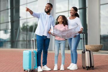 Obraz Happy black family traveling with kid, holding map - fototapety do salonu