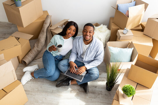 Relocation concept. African american couple using laptop to plan design of their new apartment on moving day, above view