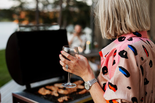 Woman holding wine glass and barbecuing meat