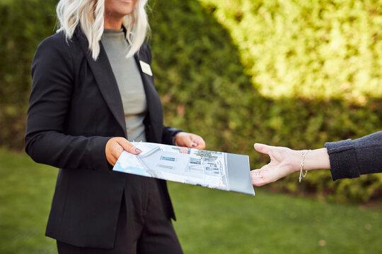 Estate agent holding house brochure