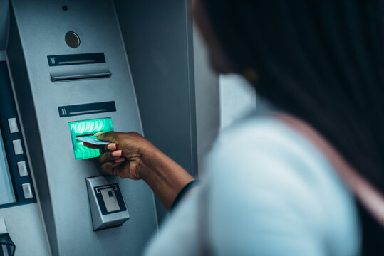 African american woman using credit card and withdrawing cash at the ATM