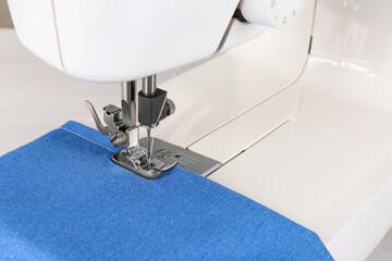 Fototapeta Modern sewing machine with blue cloth, closeup obraz