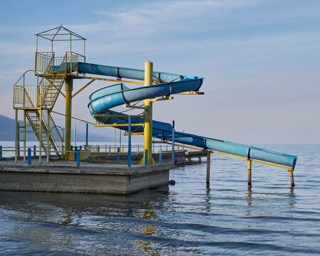 Old abandoned blue waterslide going from pier into body of water