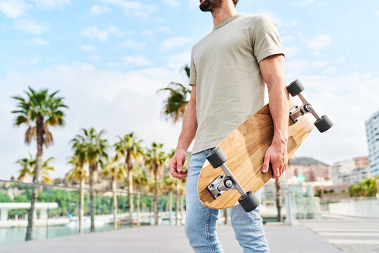 man with skateboard standing on city lakeside