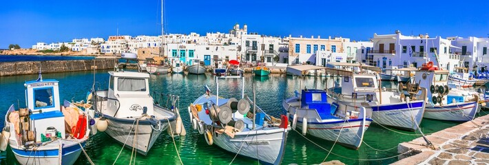 Fototapeta Greece travel. Cyclades, Paros island. Charming fishing village Naoussa. view of old port with  boats and street taverns by the sea. may 2021 obraz
