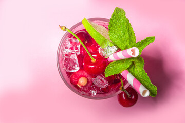 Obraz Cold and refreshing summer drink. Cherry cola, limeade, mojito lemonade cocktail with lime and cherries on colorful bright pink background - fototapety do salonu