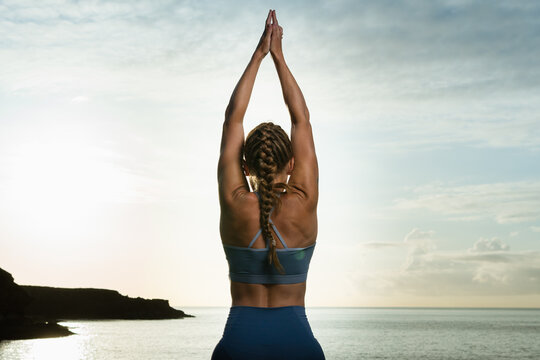 Faceless woman performing Tree with Arms Up pose against sea