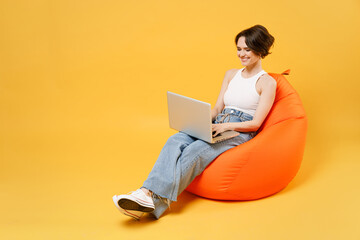 Fototapeta Young smiling woman 20s with bob haircut wearing white tank top shirt using laptop pc computer chat online browsing surfing internet sit in orange bag chair hold face isolated on yellow background obraz