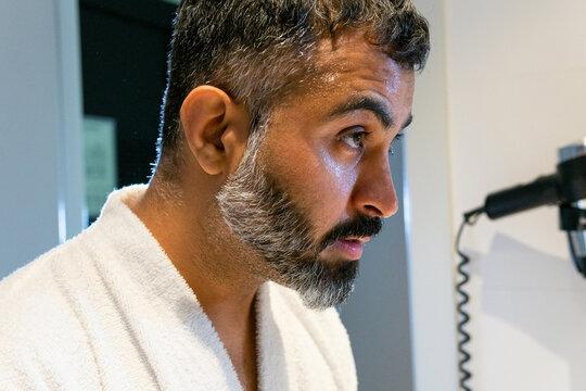 Mature man washing face in bathroom