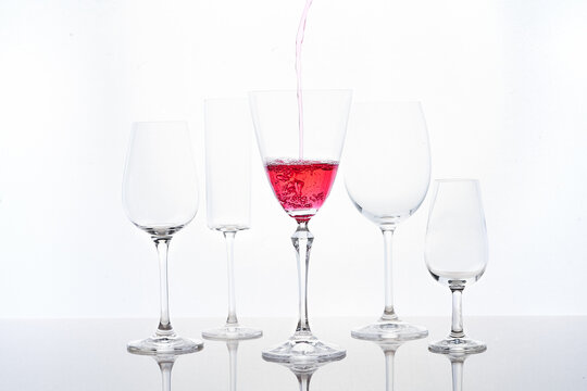 Red cocktail filling into goblet placed near different crystal glasses