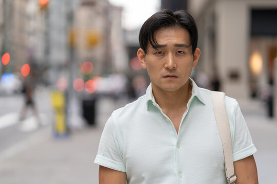Young Asian man in city serious face portrait