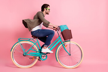 Obraz Full length body size profile side view of attractive cheerful guy riding bike isolated over pink pastel color background - fototapety do salonu