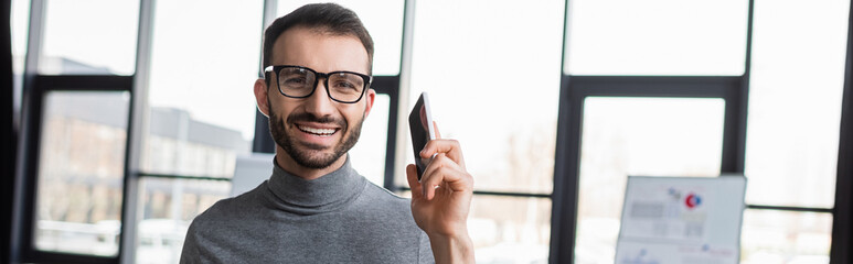 Cheerful businessman with cellphone looking at camera in office, banner - fototapety na wymiar