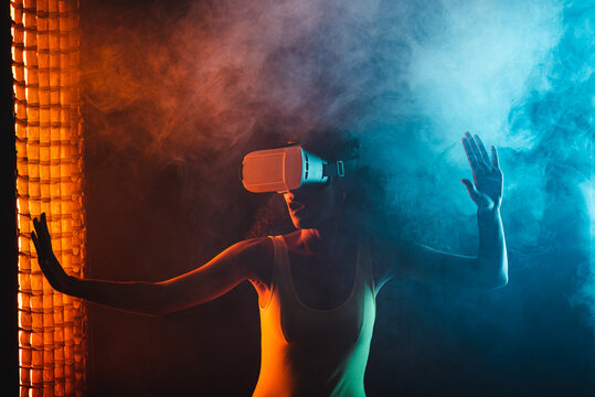 Unrecognizable amazed black woman experiencing virtual reality in goggles