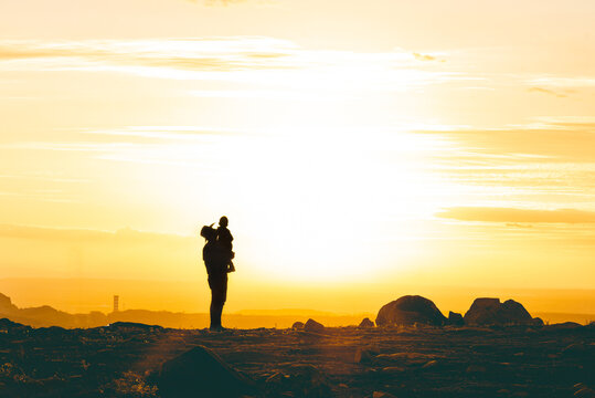 Unrecognizable father holding son in air in desert at sunset