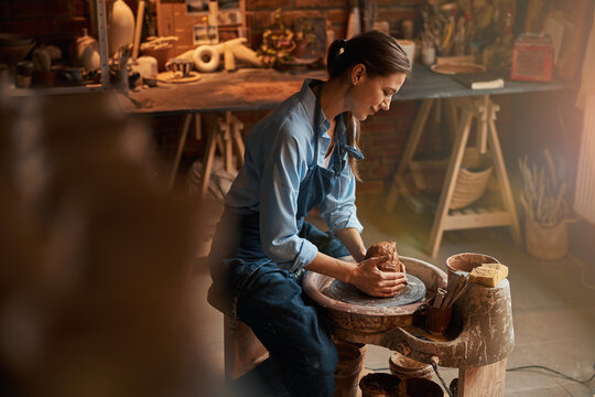 Charming Caucasian craft woman wearing apron modeling ceramic earthenware product in pottery workshop