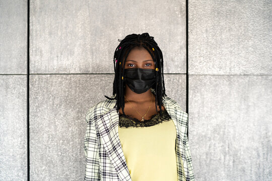 Upset black woman with dreadlocks against concrete wall