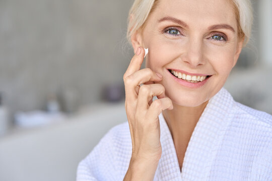 Headshot portrait of attractive senior adult older blonde lady wears bathrobe in bathroom applying nourishing tightening lifting face skin care cream treatment, looking at camera.
