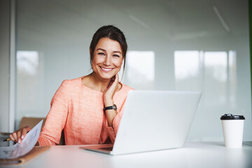 Fototapeta Young attractive female business analyst in pink jacket working at the laptop in cozy luxury office interior obraz