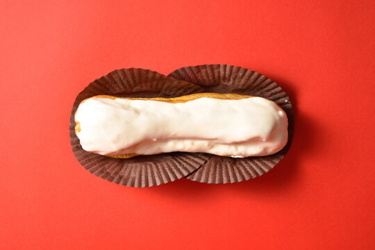 Classic French dessert eclair with white chocolate on top filled with custard, served on red background. Top view. Copy space image