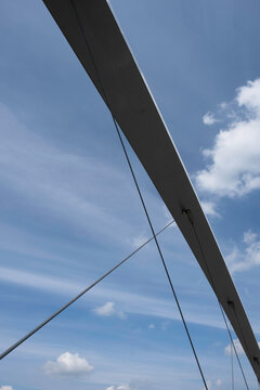Metal arch construction with cables of the of the 'Hoge Brug' (High Bridge), a modern bridge for pedestrians and cyclists over the Meuse River in Maastricht, the Netherlands. Blue cloudy sky