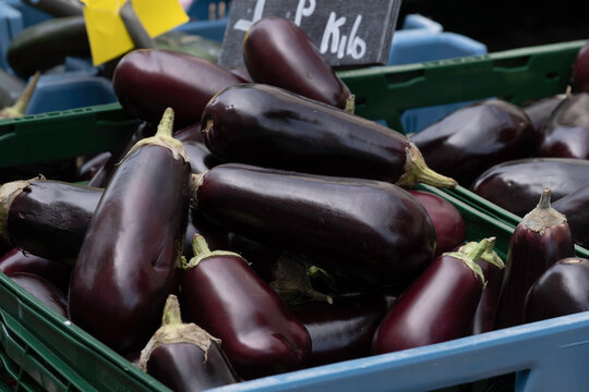A blue plastic crate full of dark purple aubergines on display at a market stall