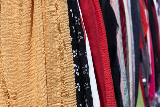 Woven fabrics in all kinds of colors and patterns at a market. Focus on the left orange-yellow fabric