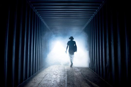 Silhouette of a man in a dark hazy underground corridor