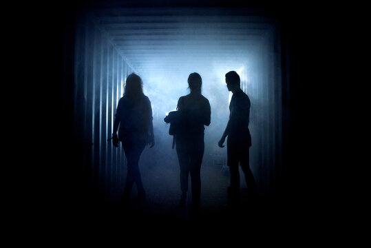 Silhouette of people in a dark misty underground creepy corridor