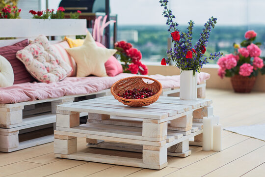 cozy beautiful pallet furniture with colorful pillows at summer patio