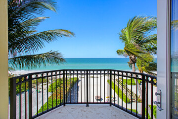 Balcony with beach view and palm trees well manicured landscaping