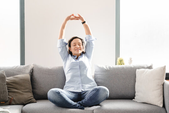 Middle-aged mature caucasian woman sitting on the couch sofa in living room, relaxing and having rest , stretching in yoga position after working day. Female freelancer having break after remote job